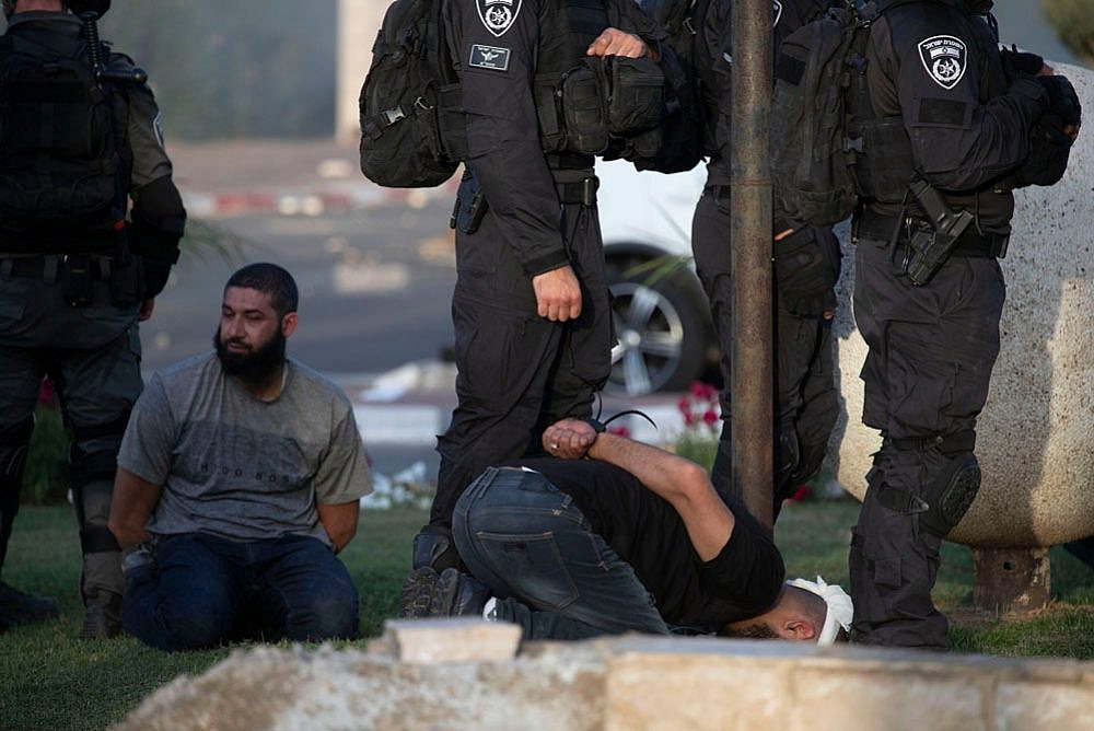 Israeli officers blindfold a Palestinian citizen of Israel during violent confrontations in Lydd, central Israel. (Oren Ziv)