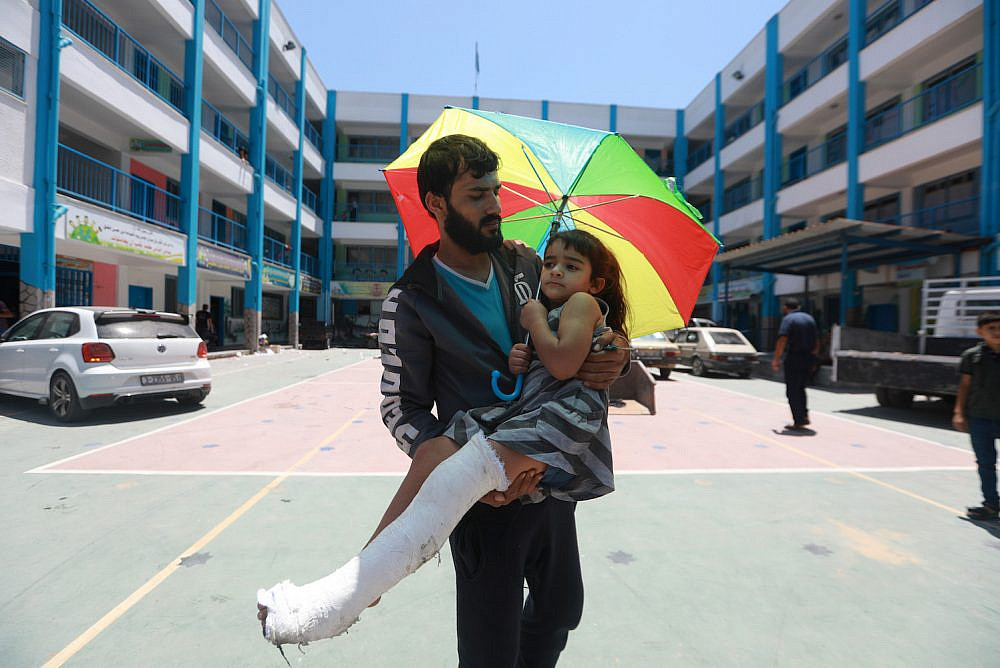 A Palestinian man carries his wounded daughter at an UNRWA school in Gaza City, where families who were displaced by Israeli shelling fled to take shelter, May 14. 2021. (Mohammed Zaanoun/Activestills)
