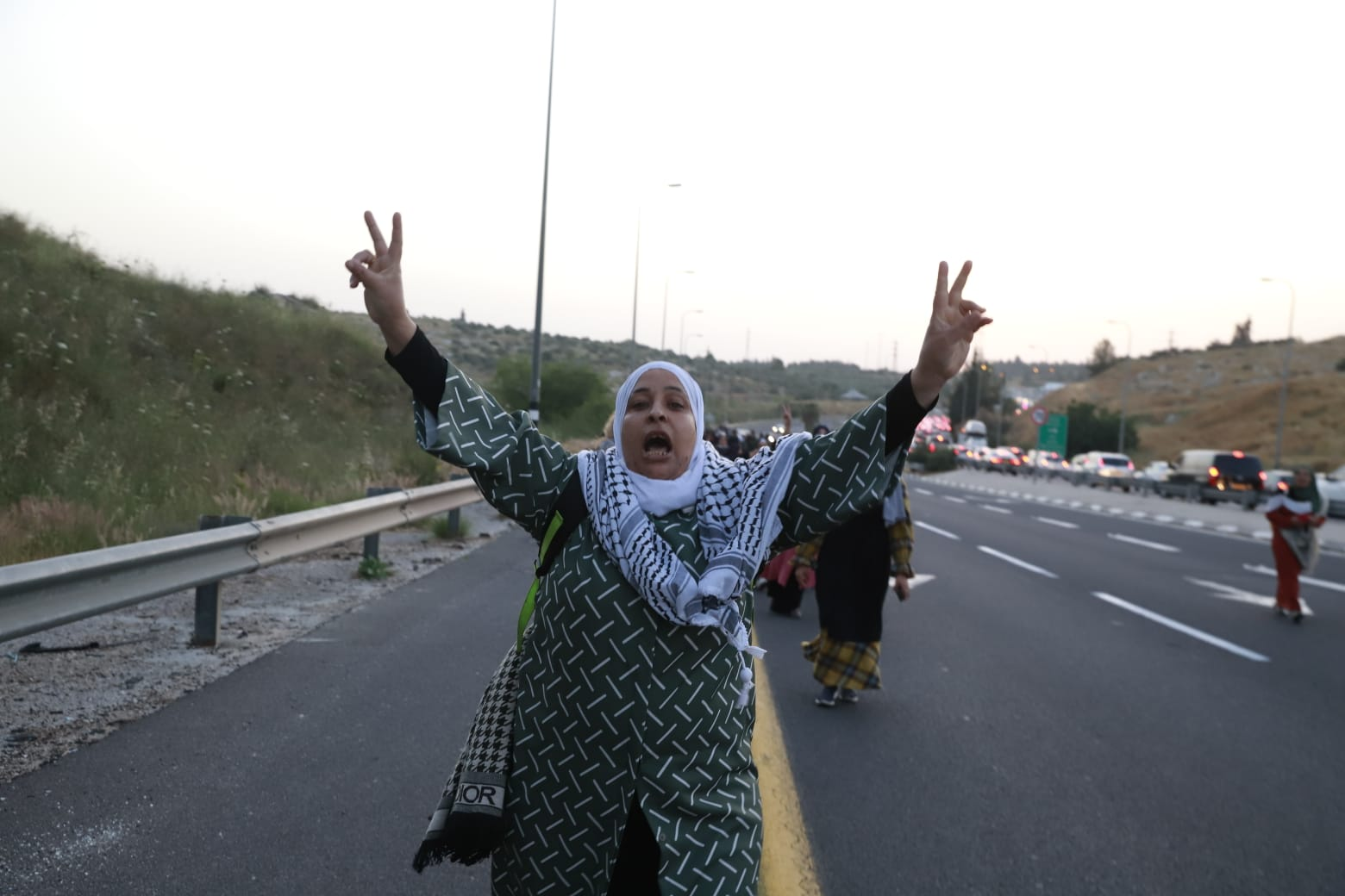 A Palestinian woman marches on Road 443 in the West Bank toward Jerusalem for Ramadan prayers after Israeli police blocked traffic into the city to prevent additional Palestinians from entering, May 8, 2021. (Oren Ziv)