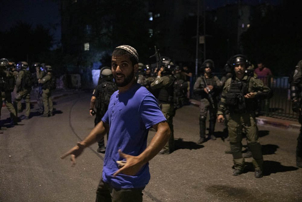 A right-wing Israeli seen standing in front of Israeli Border Police officers during attacks by security forces, rightists, and settlers on Palestinians in the city of Lyd, central Israel, May 13, 2021. (Oren Ziv)