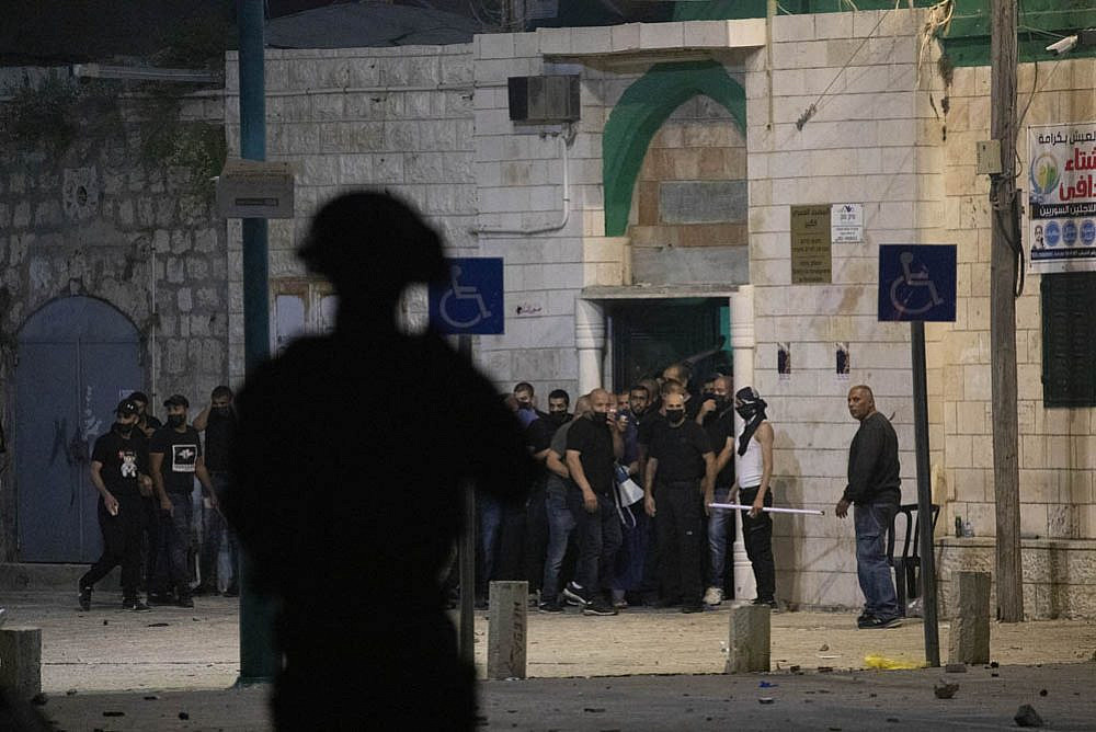 Palestinian residents of Lyd protect a local mosque during confrontations with Border Police officers and extremist settlers, May 13, 2021. (Oren Ziv)