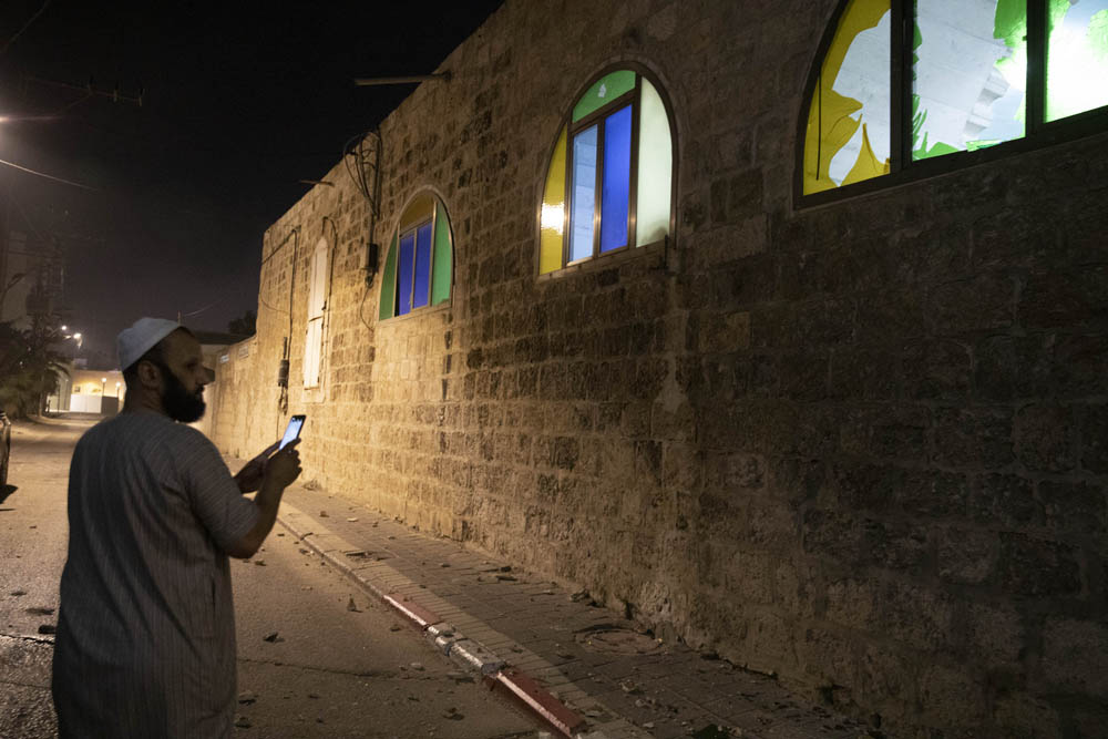 A Palestinian assess the damage to a mosque in the unrecognized village of Dahmash, near the city of Lyd in central Israel, which was attacked by settlers, May 13, 2021. (Oren Ziv)