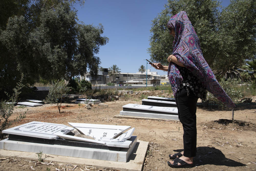 A Palestinian woman photographs a vandalized gravestone in a Muslim cemetery in Lydd, central Israel. (Oren Ziv)