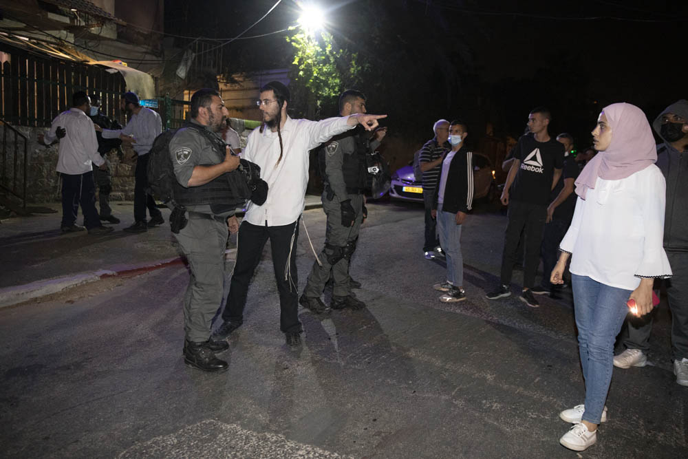 Muna El-Kurd (right) looks on as an Israeli settler speaks to an Israeli police officer during a vigil against the upcoming eviction of Palestinian families from Sheikh Jarrah, East Jerusalem, May 4, 2021. (Oren Ziv)