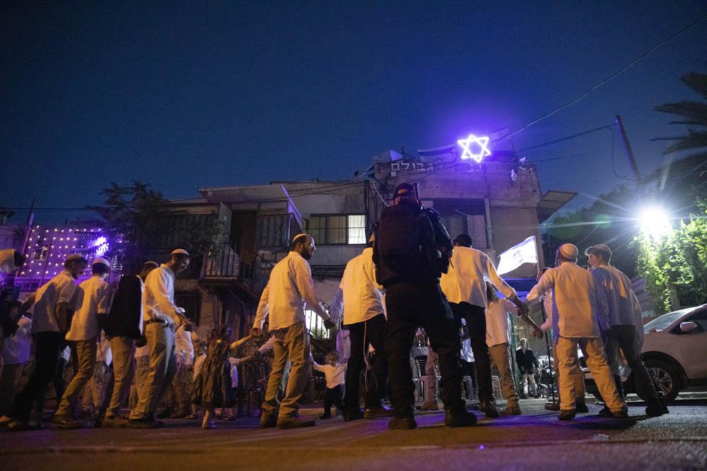 Israeli settlers celebrate the Sabbath under the protection of armed Israeli police officers in the East Jerusalem neighborhood of Sheikh Jarrah, May 7, 2021. (Oren Ziv)