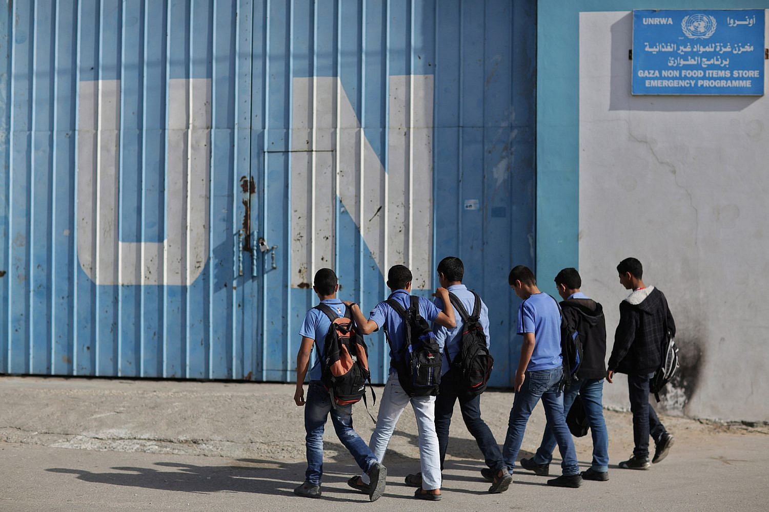 Palestinian students walk past a UN distribution center in the Jabaliya refugee camp in the northern Gaza Strip, April 6, 2013. (Wissam Nassar/Flash90)