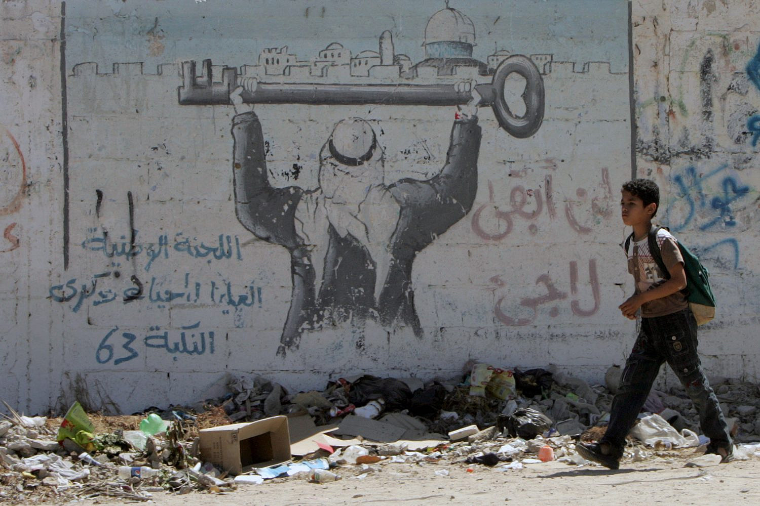"Palestinian boy walks front of graffiti that reads 'Returning' as Palestinians attend ""Camp of Return"" to mark refugees' ties to their lost land, in Rafah, southern Gaza Strip, May 12, 2013. (Abed Rahim Khatib/Flash90)"
