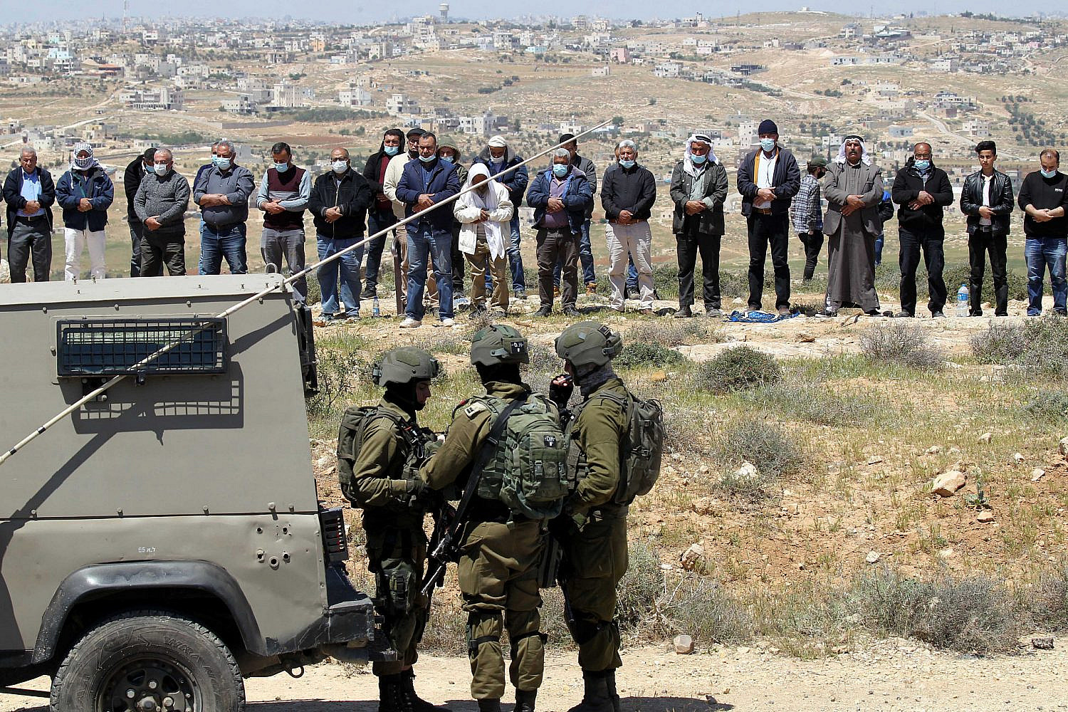 Israeli security forces stand while Palestinians pray before a protest against the settlements near Yatta, in the West Bank, April 9, 2021. (Wisam Hashlamoun/Flash90)