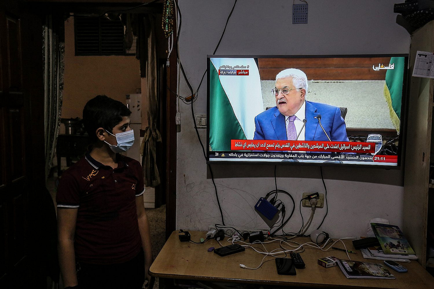 A Palestinian family watch the speech of President Mahmoud Abbas regarding the Palestinian elections at their home in Rafah, in the Gaza Strip, April 29, 2021. (Abed Rahim Khatib/Flash90)