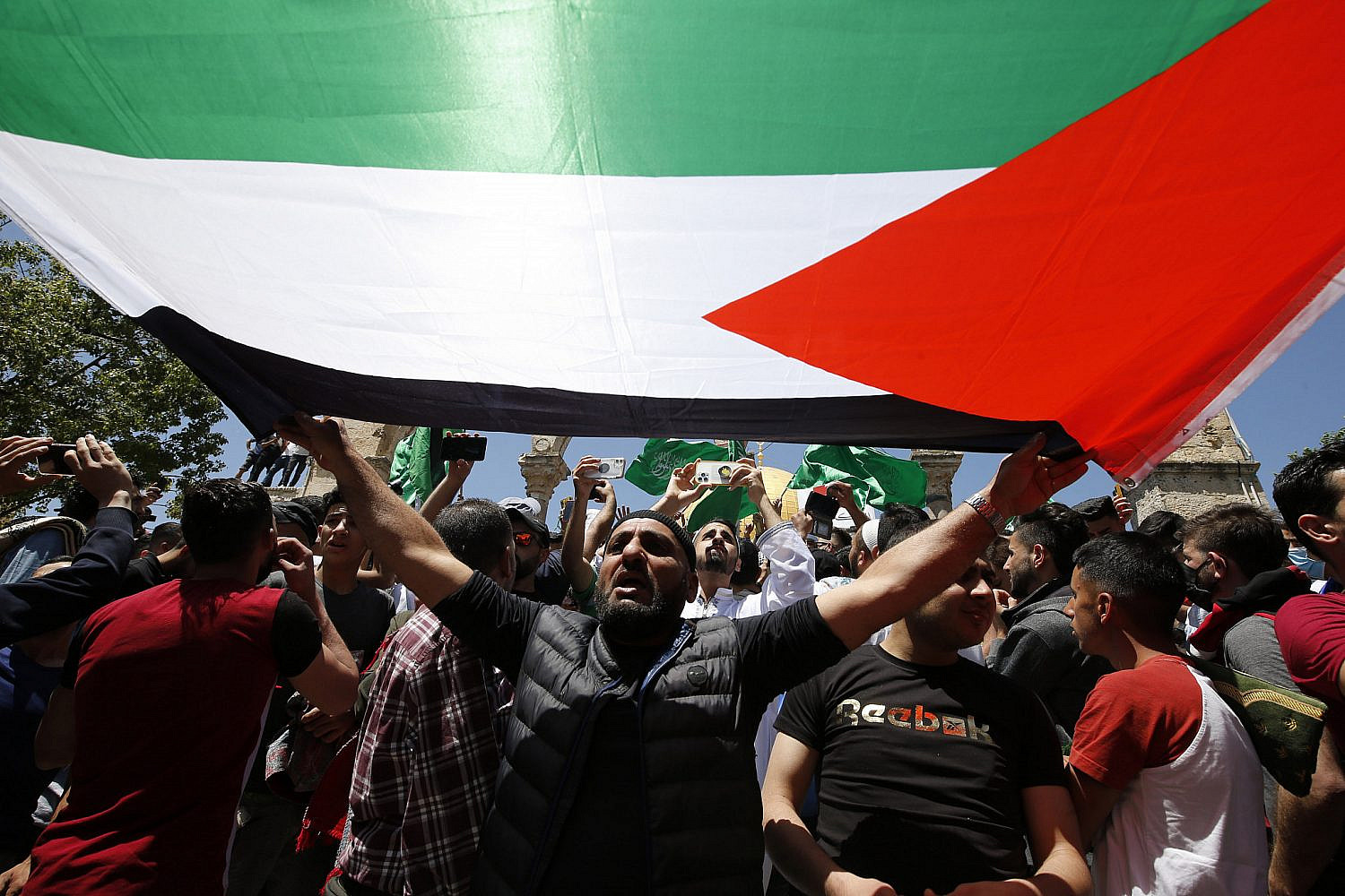 Palestinians hold Hamas flags after performing the last Friday prayer of Ramadan to protest over the possible eviction of Palestinian families from homes in the East Jerusalem neighborhood of Sheikh Jarrah, May 7, 2021. (Jamal Awad/Flash90)