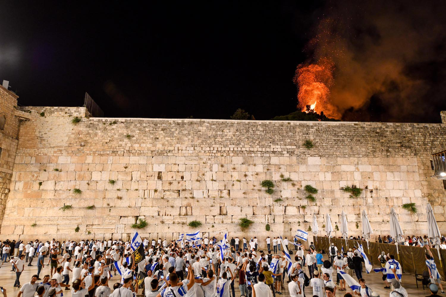 Israelis celebrate Jerusalem Day at the Western Wall as a blaze is seen from the al-Aqsa Compound, Jerusalem, May 10, 2021. (Mendy Hechtman/Flash90)