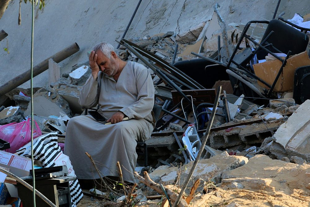 Palestinians check the damage caused after a 15-floor building was destroyed in an Israeli airstrike in Gaza City, on May 13, 2021. (Atia Mohammed/Flash90)