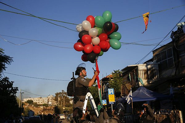 An Israeli police officer tries to take down balloons released by Palestinians in the East Jerusalem neighborhood of Sheikh Jarrah on May 15, 2021. (Jamal Awad/Flash90)