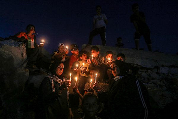 Palestinian children light candles during a protest near destroyed buildings in Rafah, Gaza, May 25, 2021. (Abed Rahim Khatib/Flash90)
