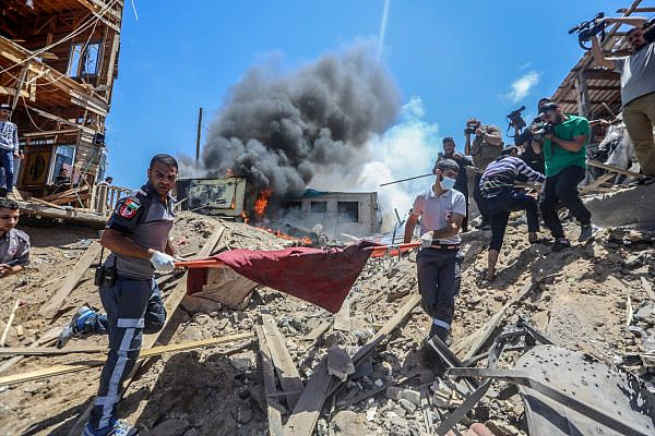 Palestinians carry the wounded following a deadly Israeli airstrike on a cafe on the beach in Gaza City, May 17, 2021. (Mohammed Zaanoun/Activestills)