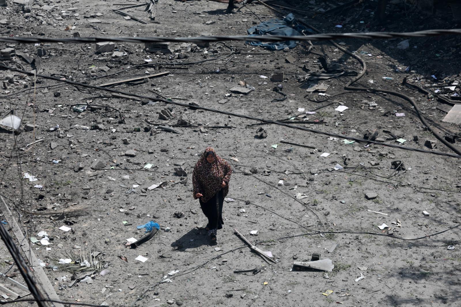 A Palestinian woman walks through the rubble following an Israeli airstrike, May 16, 2021. (Mohammed Zaanoun/Activestills)