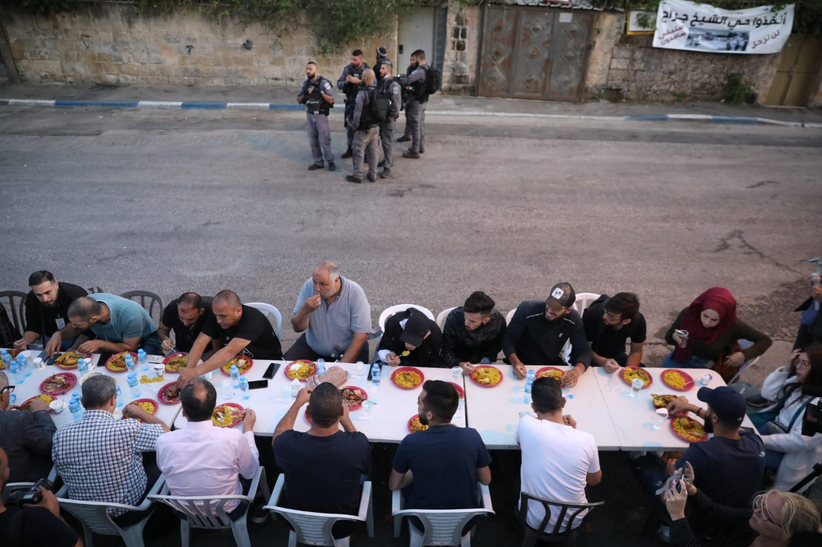 Palestinians hold their nightly Iftar meal to break the Ramadan fast outside a Palestinian home previously taken over by Israeli settlers in the East Jerusalem neighborhood of Sheikh Jarrah, May 7, 2021. The Iftar was part of a nightly vigil held by Palestinians in the neighborhood to protest the planned eviction of four more Palestinian families fro their homes in the neighborhood. (Oren Ziv)