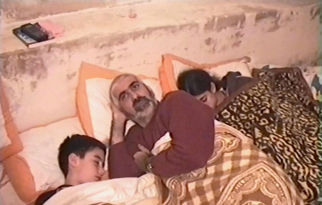 Dima Srouji, her brother, and her father sleep in the basement of their home in Beit Jala, the occupied West Bank, to protect themselves from Israeli bombs during the Second Intifada. (Courtesy of Dima Srouji)