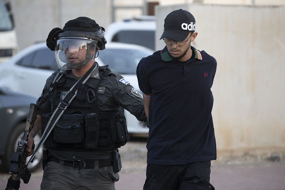 An Israeli police officer arrests a Palestinian during confrontations in the city of Lydd, central Israel. (Oren Ziv)
