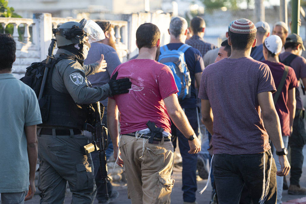 Settlers and right-wing activists walk alongside Israeli police officers in Lydd, central Israel, May 13, 2021. Many of the settlers came from settlements in the occupied West Bank and spent the evening attacking Palestinians in the city under the eye of Israeli security forces. (Oren Ziv)