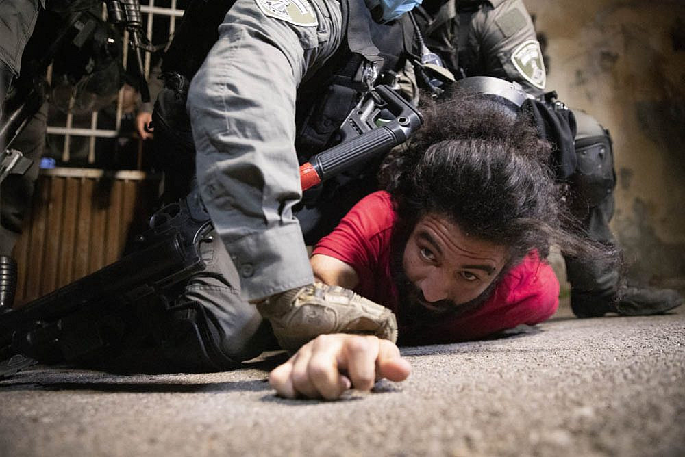 Israeli police pins a Palestinian resident of Sheikh Jarrah to the ground during a vigil against the upcoming evictions in the neighborhood, May 4, 2021. (Oren Ziv)