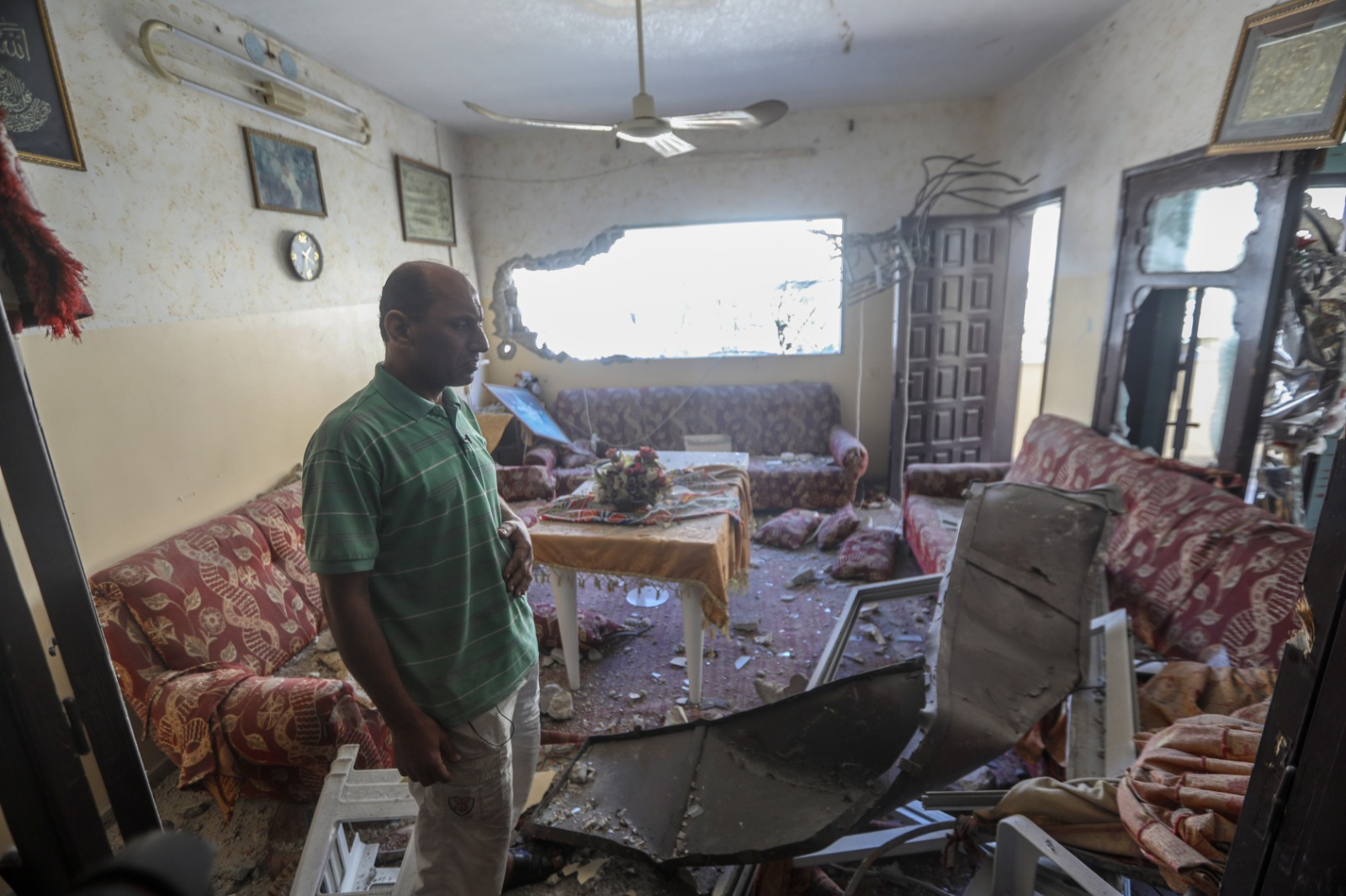 A Palestinian man seen in his home after it was destroyed by an Israeli airstrike, May 15, 2021. (Mohammed Zaanoun/Activestills)