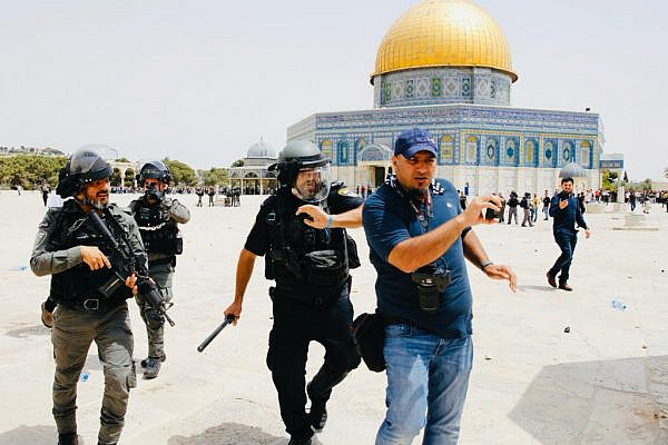 Israeli police beat Palestinian journalist Ahmad Gharabli at Al-Aqsa Mosque compound in Jerusalem, on May 21, 2021. (Suliman Khader)