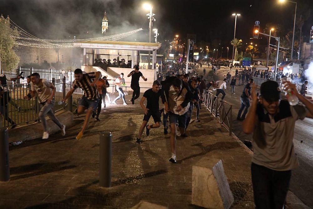 Palestinian demonstrators flee after Israeli security forces fire tear gas outside Damascus Gate, Jerusalem, May 8, 2021. (Oren Ziv)