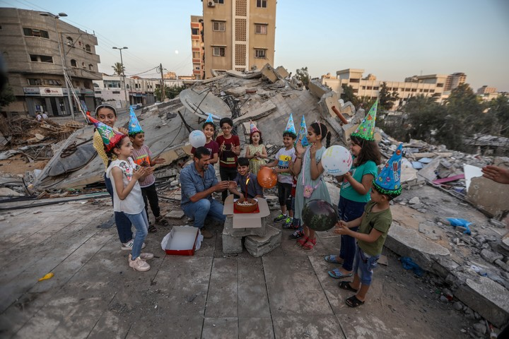 A Palestinian family holds a birthday party in the rubble of their house, destroyed by Israeli bombs, in Gaza City, May 25, 2021. (Mohammed Zaanoun/Activestills)