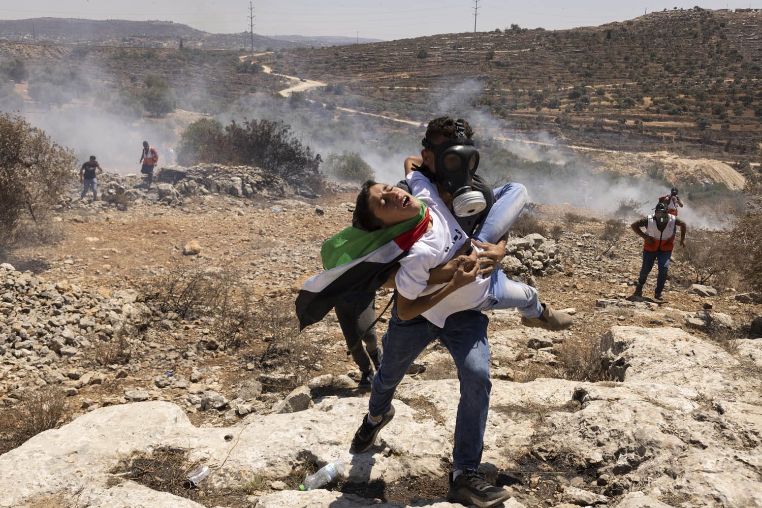 A Palestinian demonstrator is carried during a protest against the settlement outpost of Eviatar, Beita, West Bank, June 25, 2021. (Oren Ziv)