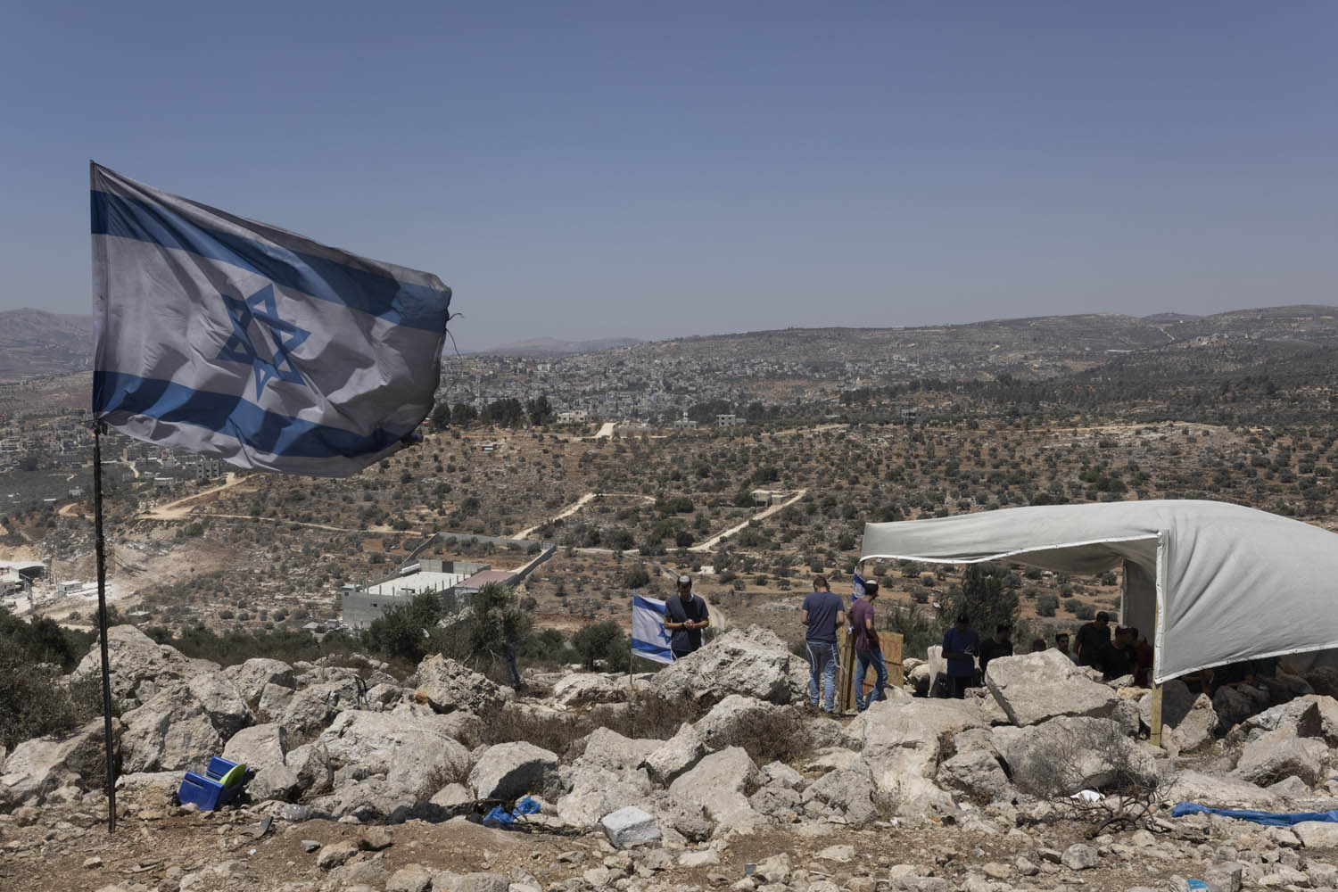Settlers in the outpost Eviatar overlook the area near the Palestinian town of Beita, northern West Bank, June 28, 2021. (Oren Ziv)