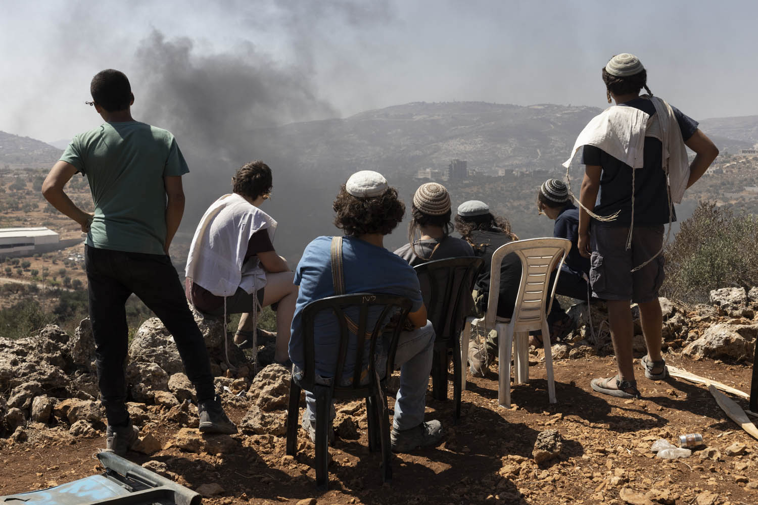 Settler youth in the outpost of Eviatar watch as smoke rises from burning tires near the Palestinian town of Beita, West Bank, June 28, 2021. (Oren Ziv)