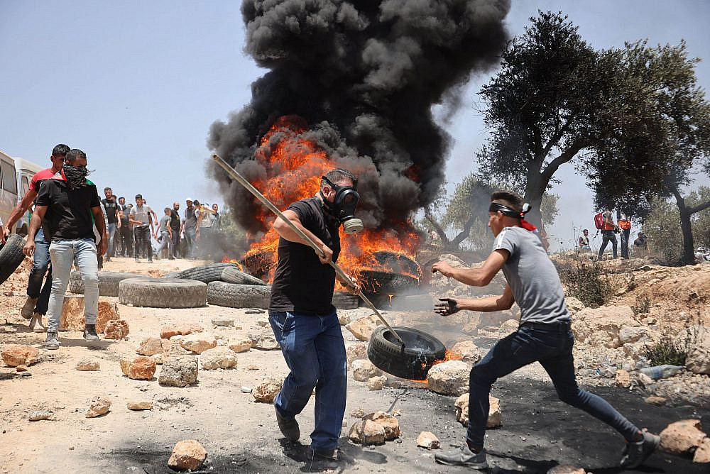 Palestinian protesters burn tires during a protest against the settlement outpost of Eviatar, West Bank, June 11, 2021. (Oren Ziv)