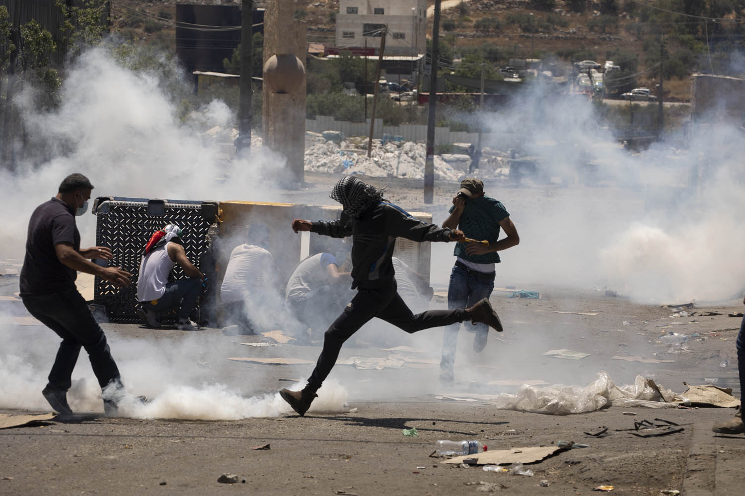 Palestinians throw stones and dodge tear gas shot by Israeli soldiers in the West Bank town of Beita, during a protest against the settlement outpost of Eviatar, June 18, 2021. (Oren Ziv)