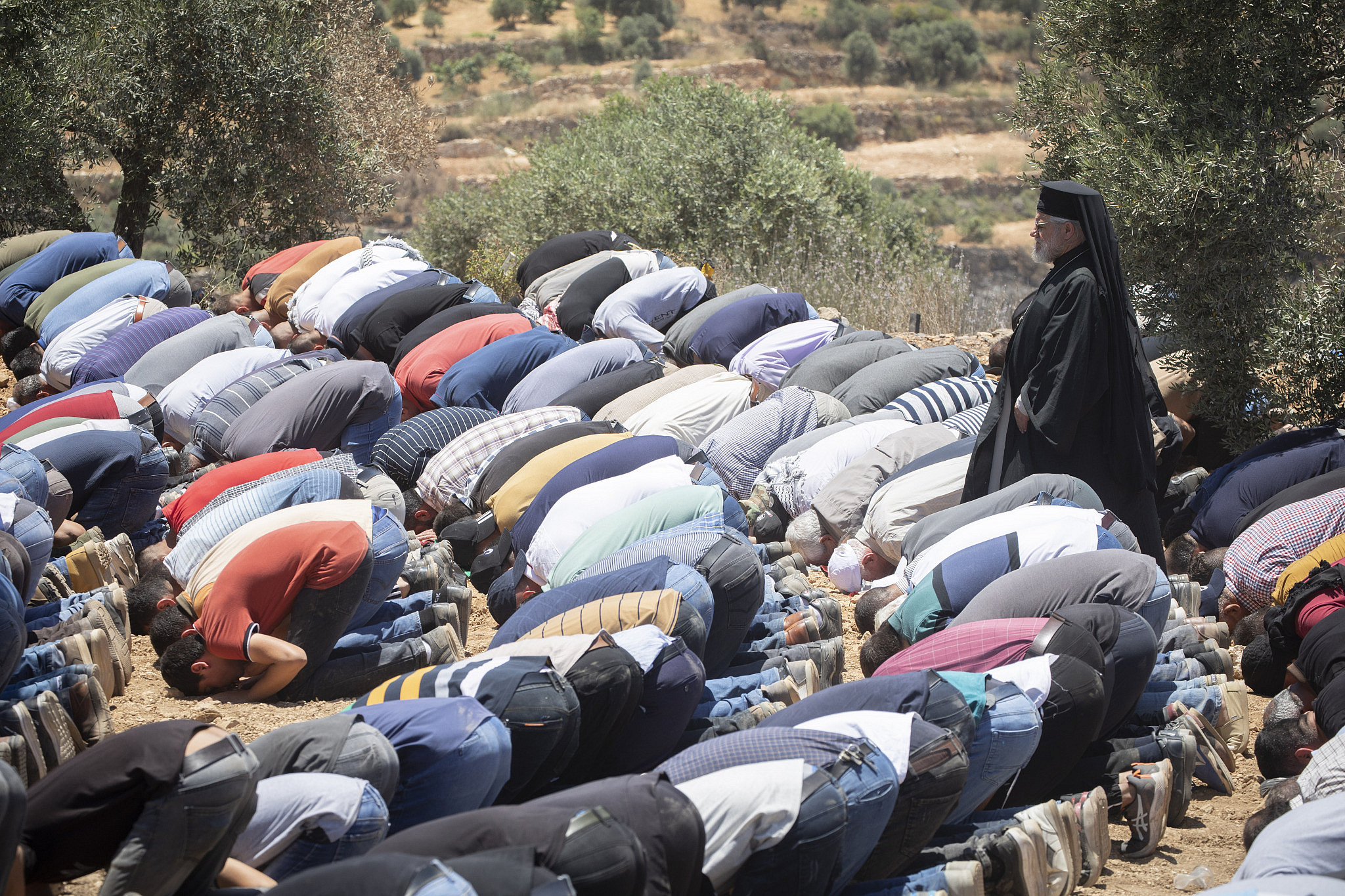A Palestinian priest who arrived in Beita to show support for the protesters there walks among Muslim worshippers as they pray before their daily demonstration against the Eviatar outpost, West Bank, June 29, 2021. (Oren Ziv)
