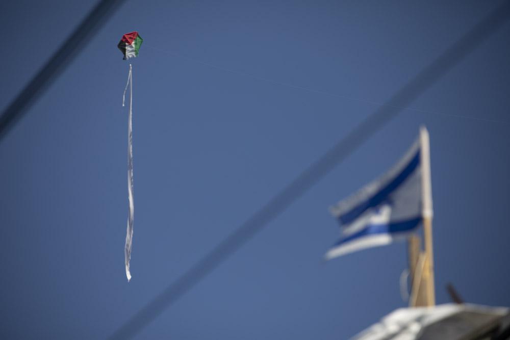 Un aquilone con una bandiera palestinese vola sopra una casa palestinese che è stata occupata dai coloni israeliani a Sheikh Jarrah, Gerusalemme est. (Oren Ziv)