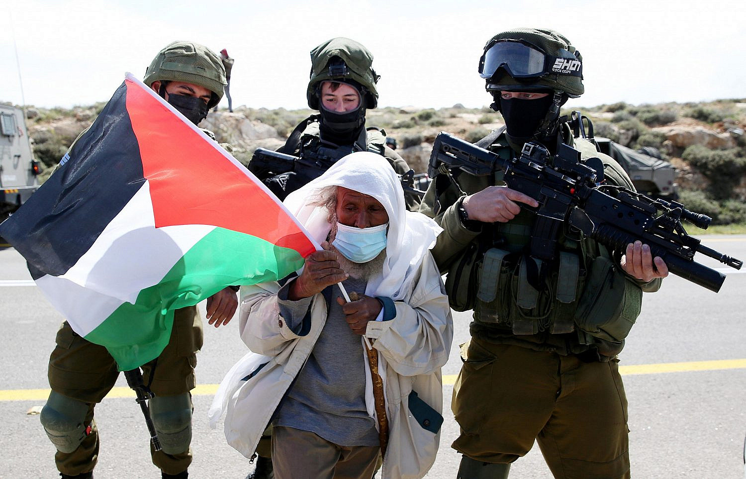 A Palestinian protester surrounded by Israeli soldiers during a protest against Israeli settlement building near the West Bank town of Yatta, near Hebron, March 12, 2021. (Wissam Hashlamon/Flash90)