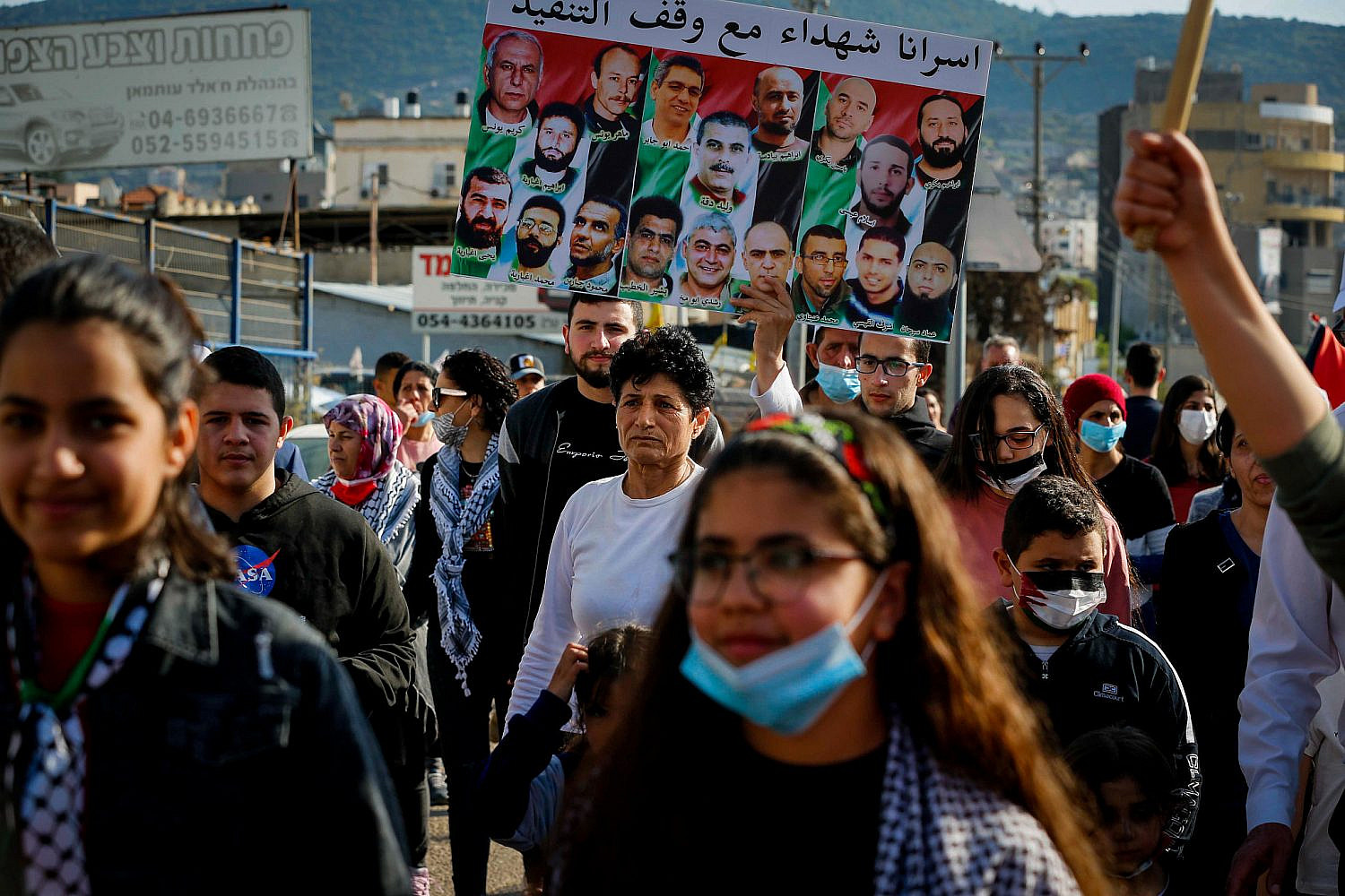 Palestinian citizens march during a protest marking Land Day, the annual event commemorating the Israeli police killings of six protesters during mass protests in 1976 against plans to confiscate Arab land, in Arrabe, northern Israel, March 30, 2021. (Jamal Awad/Flash90)