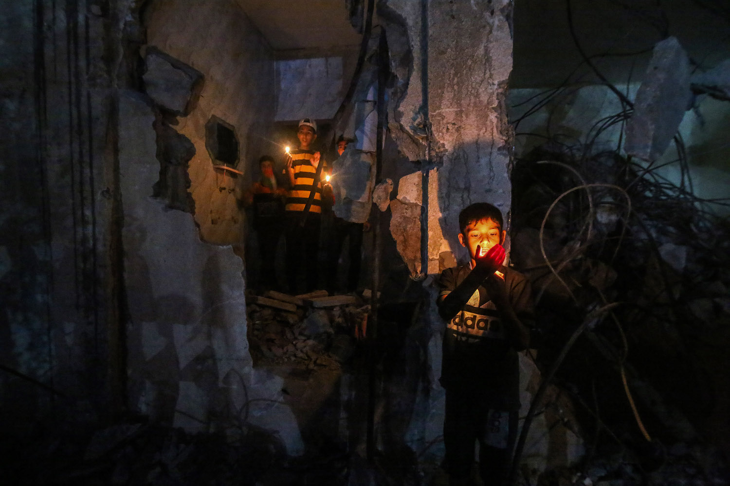 Palestinian children light candles during a protest near destroyed buildings in the southern Gaza Strip city of Rafah, May 25, 2021. (Abed Rahim Khatib/Flash90)