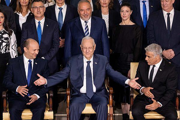 Israeli Prime Minister Naftali Bennett (left), Israeli Foreign Minister Yair Lapid (right), Israeli Presdint Reuven Rivlin (center) and other Israeli ministers pose for a group photo of the newly sworn in Israeli government, President's Residence, Jerusalem, June 14, 2021. (Yonatan Sindel/Flash90)