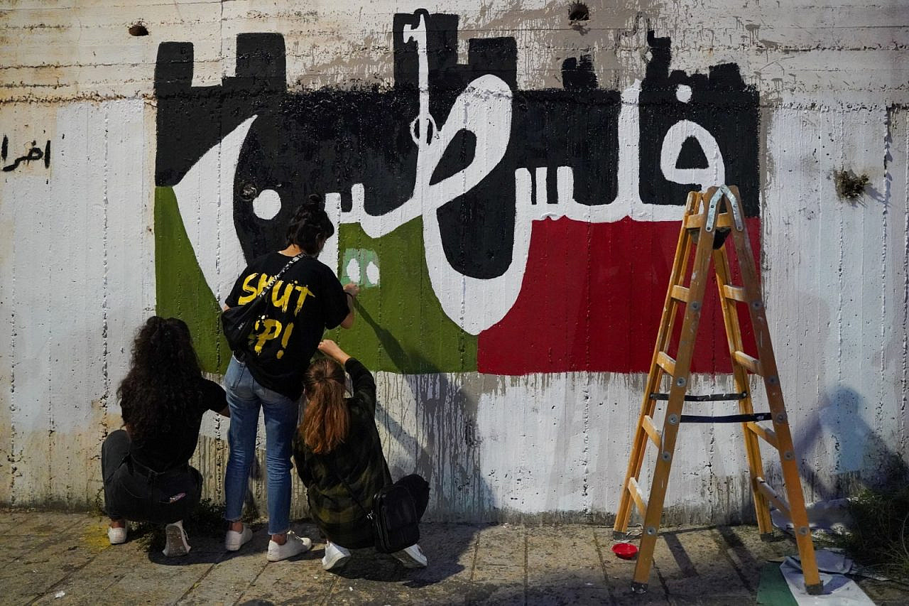Palestinian citizens of Israel paint a mural spelling