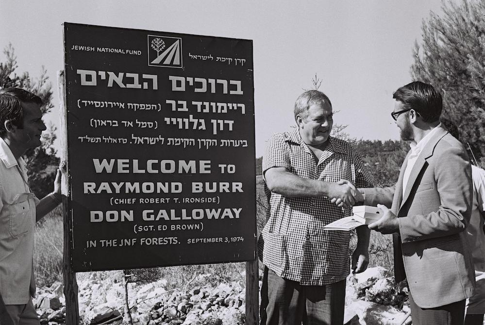 Raymond Burr and Don Galloway, the stars of American television series 'Ironside' which was hugely popular in Israel, plant a tree in Biria Forest, created by the JNF on the ruins of the villages Mughr al-Kheit, Ein A-Zeitun, Amuqa, Fir'im, and Qabaʿa, 1974. (Moshe Milner/GPO)