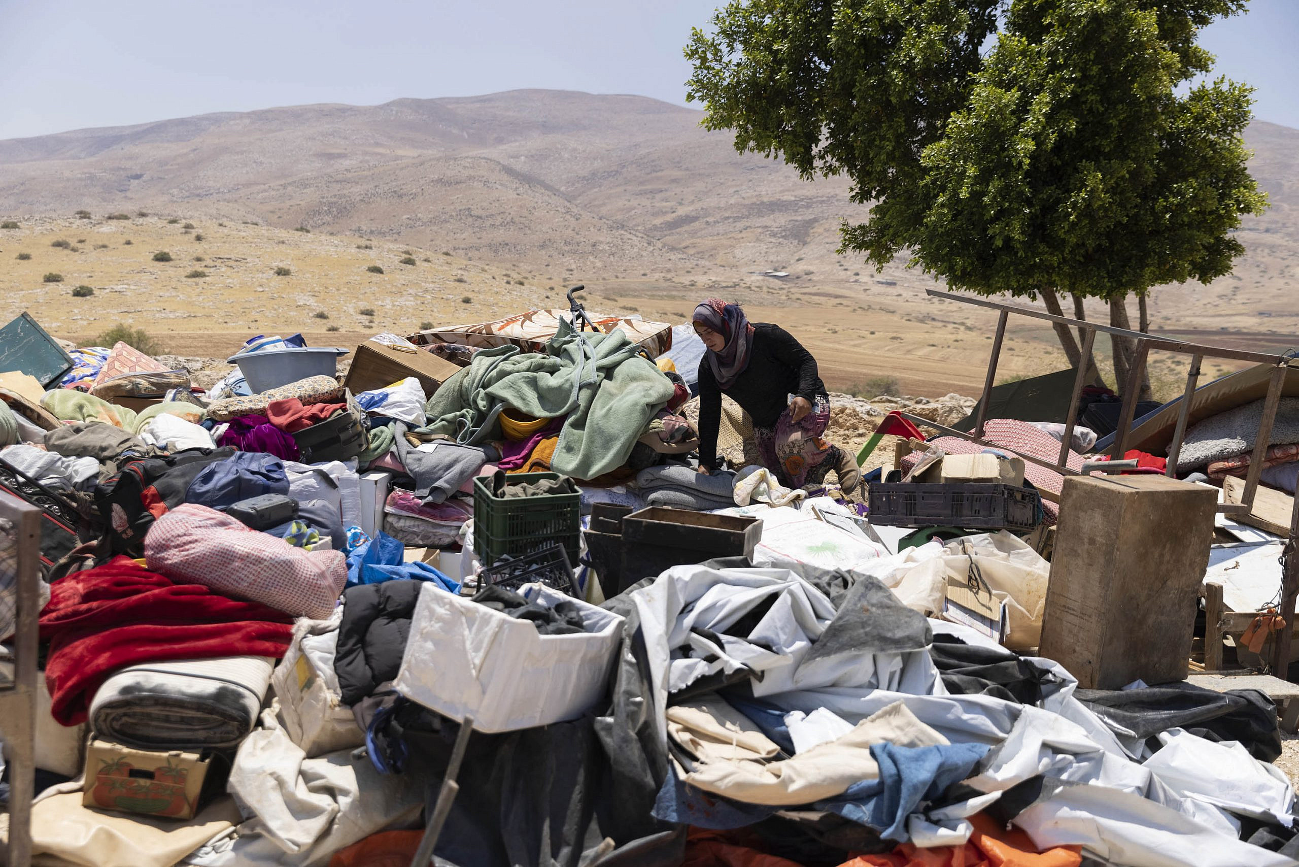 A Palestinian resident of Humsa al-Fuqa sifts through her belongings a day after the Israeli army demolished the entire community in the occupied Jordan Valley, July 8, 2021. (Oren Ziv)