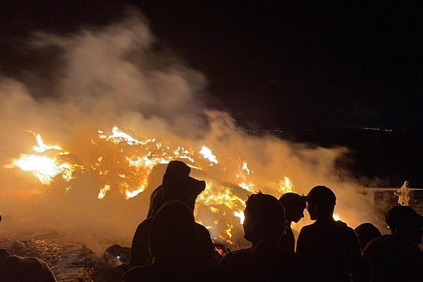 Palestinians in the village of Tuba in the South Hebron Hills look on after settlers set fire to their hay bales, June 1, 2021. (Courtesy of Jaber Awad)