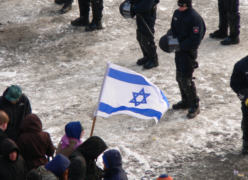 Protester holds an Israeli flag at an Antidutsche demonstration in Germany. (Fatelessfear/Wikimedia/CC-BY-SA-3.0)