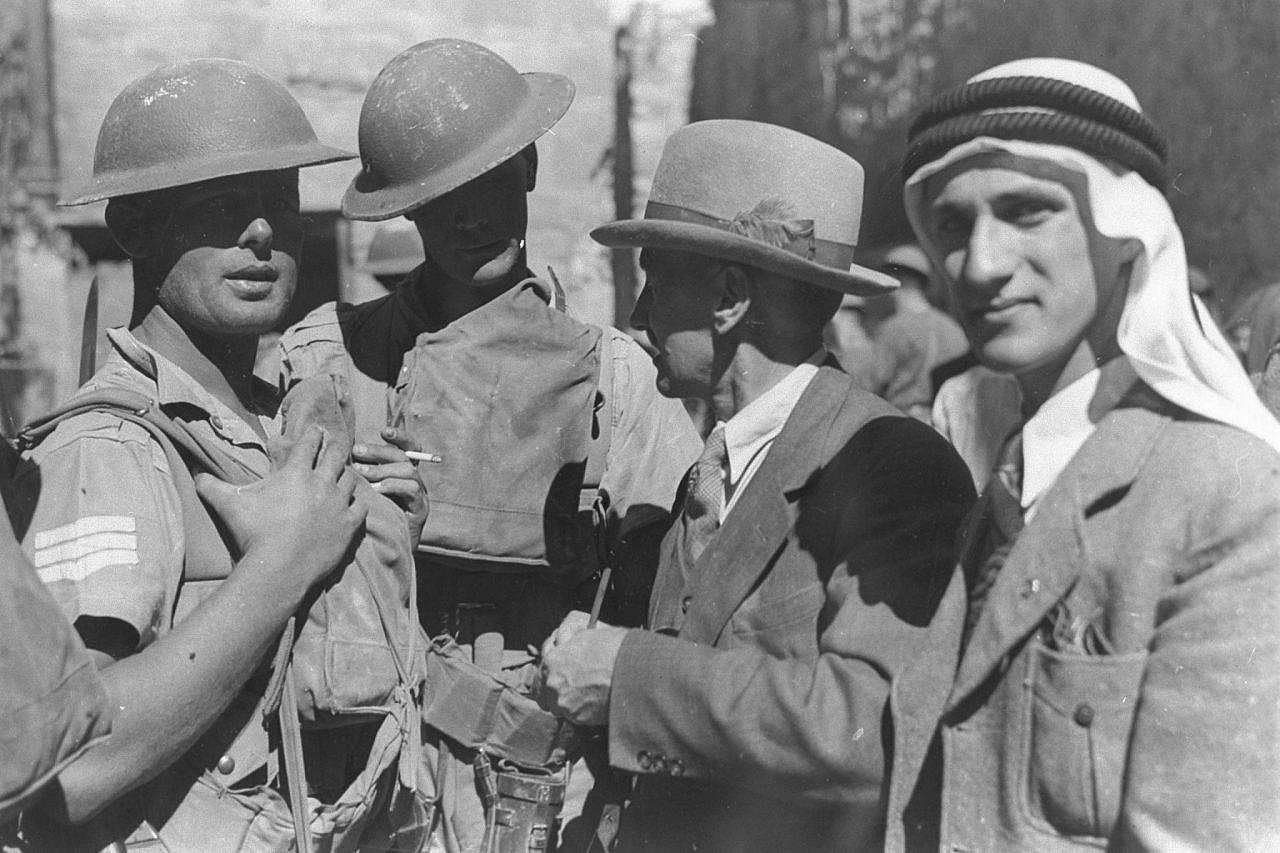 Soldati britannici in servizio nella Città Vecchia di Gerusalemme parlano con un residente palestinese (a destra) e il fotografo Eric Matson (al centro), 30 ottobre 1938. (Colonia americana/GPO)