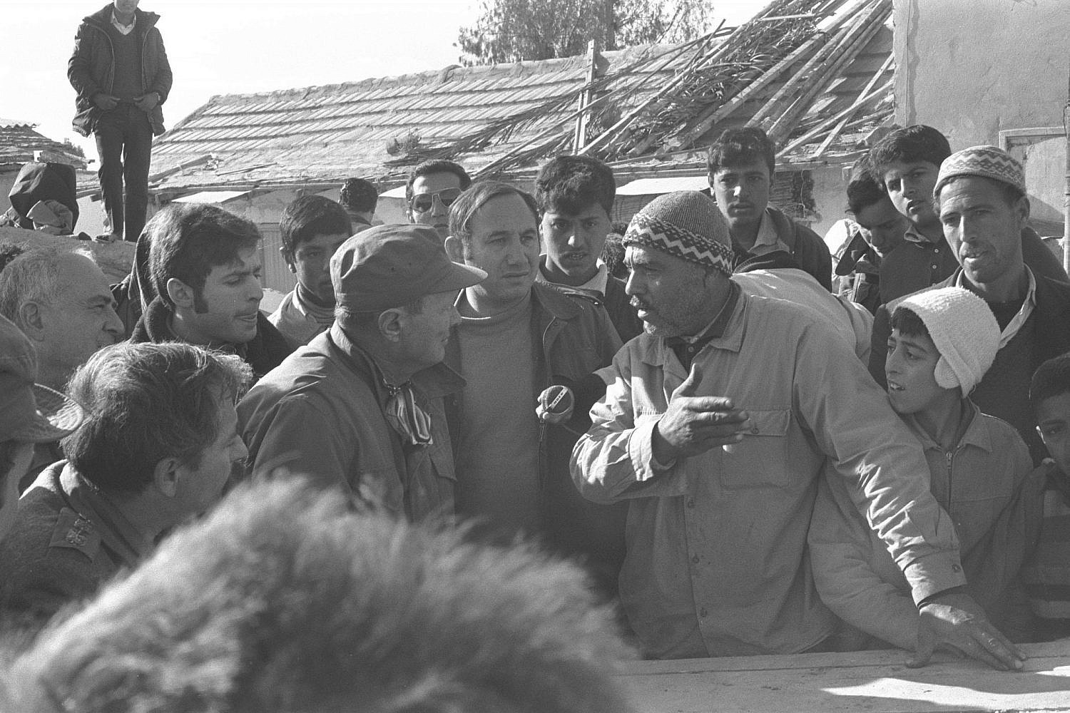 Israeli Defense Minister Moshe Dayan (l) speaks with a Palestinian Arab resident of the Rafah refugee camp in the Gaza Strip during a visit to the camp, Dec. 28, 1972. (Nissim Gabai/GPO)