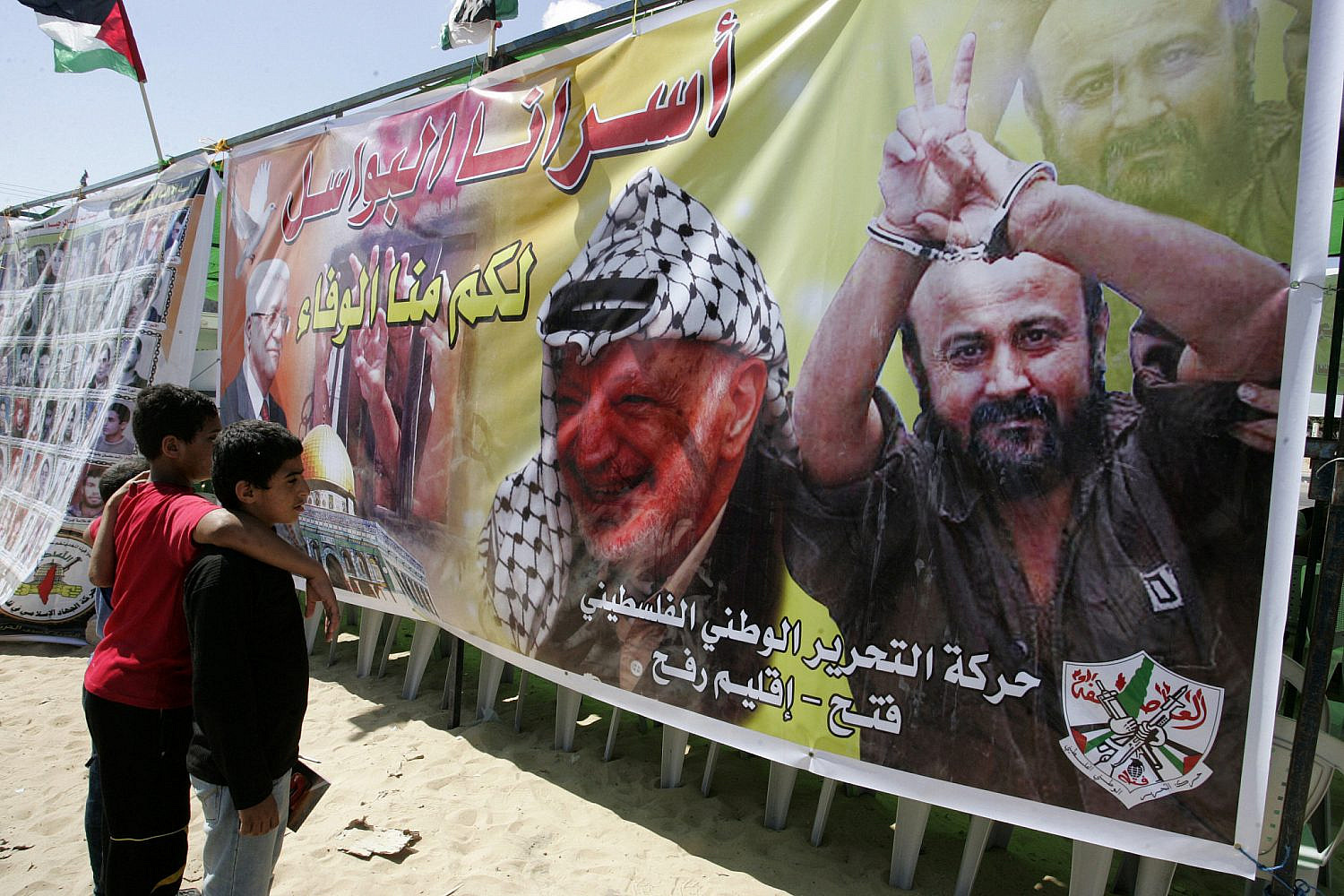 Palestinian children stand next to the image of Fatah leaders Yasser Arafat and Marwan Barghouti during a demonstration in support of prisoners on hunger strike in Israeli jails, in Rafah, Gaza Strip, Oct. 6, 2011. (Abed Rahim Khatib/Flash90)