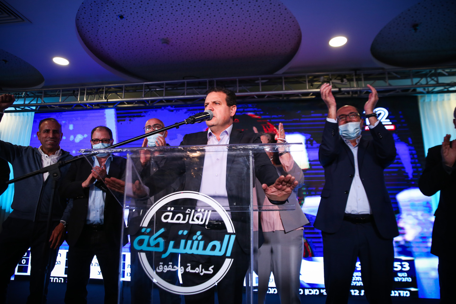 Joint List party chairman Ayman Udeh and members of the Joint List party seen at party headquarters, Shefa 'Amr, election night, March 23, 2021. (David Cohen/Flash90)