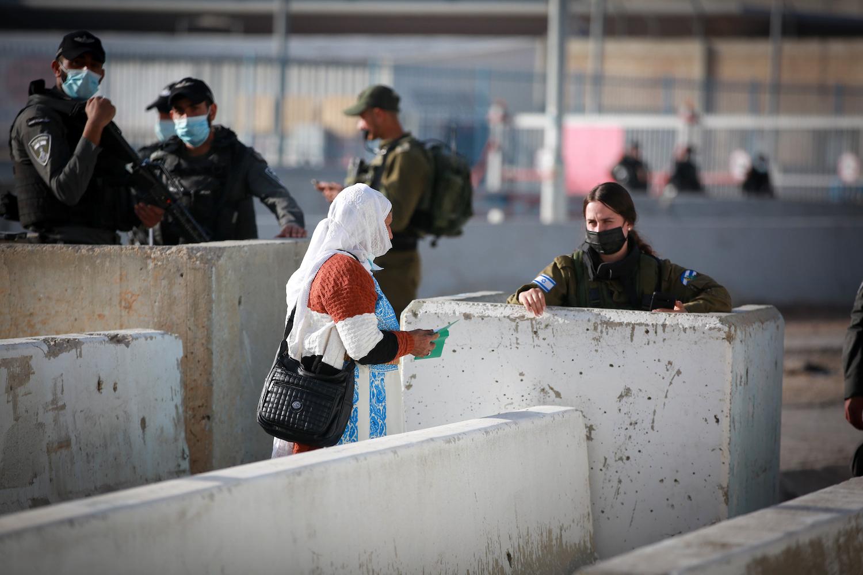 Palestinians present their documents to Israeli Border Police officers as they make their way through Israeli Qalandiya checkpoint near Ramallah, West Bank, April 16, 2021. (Flash90)